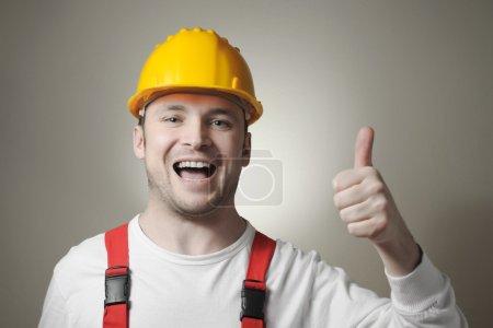 Photo pour Souriante jeune réparateur avec casque jaune - image libre de droit