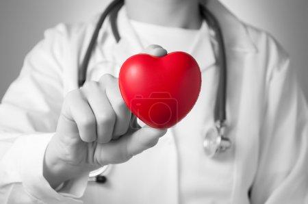 Photo pour Coeur rouge dans la main d'un médecin - image libre de droit