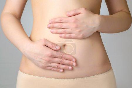 Photo pour Gros plan d'une jeune femme abdomen et mains - image libre de droit