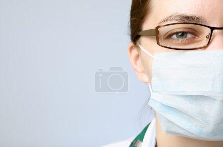Photo pour Femme médecin en masque visage regardant la caméra - image libre de droit