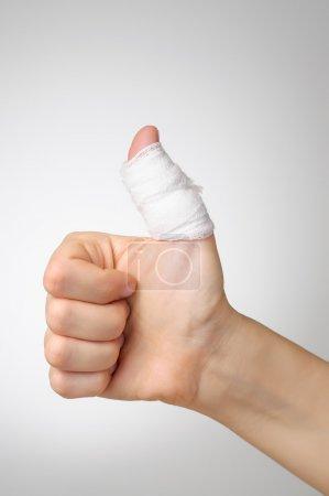 Photo pour Blessé à un pouce douloureux avec un bandage blanc - image libre de droit