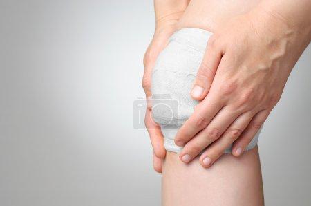 Photo pour Blessé à un genou douloureux avec un bandage de gaze blanche - image libre de droit