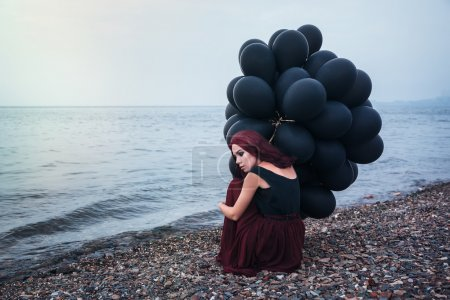 Photo for Beautiful girl walking in the beach while holding black balloons - Royalty Free Image
