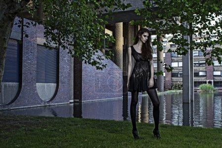 Young fashion model outdoor shoot posing wearing short black dress
