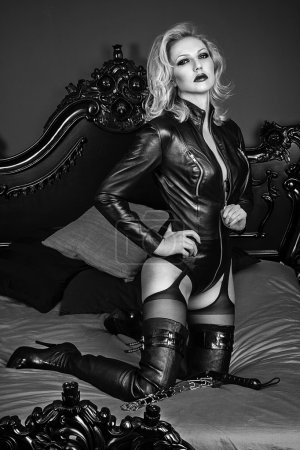 A young blond sexy lady mistress with bright red lips wearing a black leather costume laying in a bed