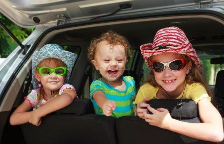 Photo pour Deux petites filles et garçon assis dans la voiture - image libre de droit