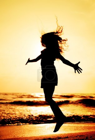 silhouette of child jumping in sunset