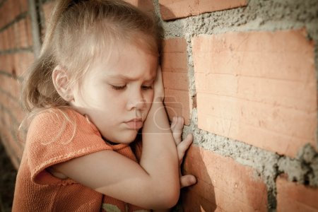 Photo for Portrait of sad little girl sitting near brick wall in the day time - Royalty Free Image