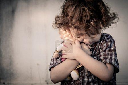 triste petit garçon serrant une poupée