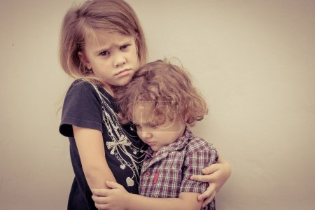 Portrait of sad little girl and little boy standing near wall in