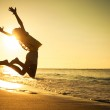 Teen girl jumping on the beach at the day time...