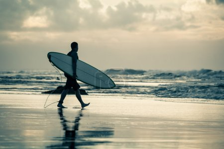 Photo for Silhouette of a surfer walking to the ocean during sunset - Royalty Free Image