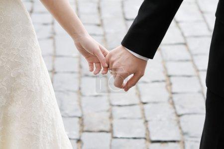Photo pour Jeunes mariés, main dans la main à l'extérieur - image libre de droit