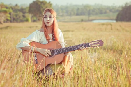 Hippie girl playing guitar on grass