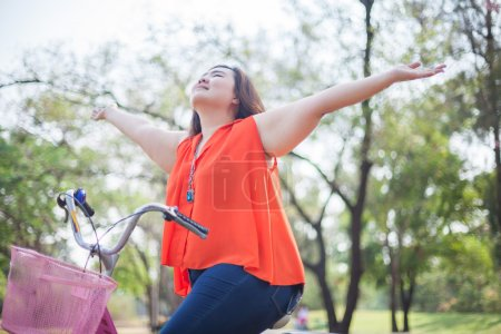 Photo for Happy fatty asian woman outstretched with bicycle outdoor in a park - Royalty Free Image
