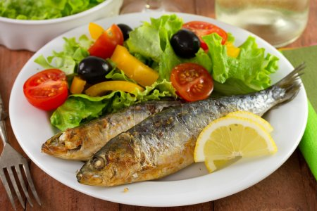 fried sardines with salad and lemon on the plate