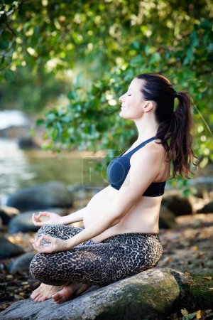 Pregnant woman practising yoga by the beach