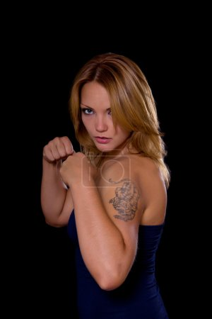 Angry tattooed woman with fists clenched, low key