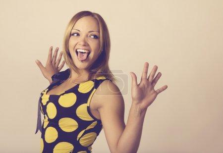 Photo pour Jeune femelle bonne humeur plaisante-collant la langue avec piercing tonique dans des couleurs chaudes - image libre de droit