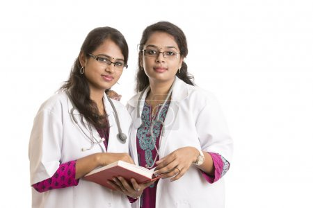 Two young Indian Female Doctors with notepad isolated on white.
