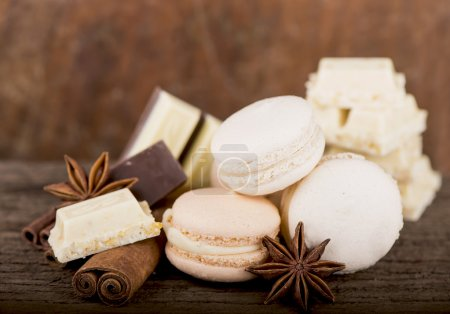 Photo for Chocolate macaroons with pieces of white and black chocolate on old wooden table - Royalty Free Image