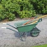 Large wheelbarrow with gardening instruments on st...