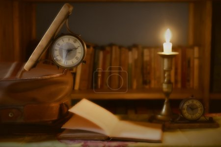 Photo for Ree time to travel and read, watch old book and suitcase illuminated by candlelight - Royalty Free Image