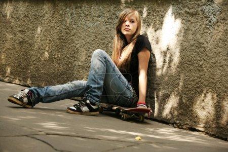 Foto de La chica con patín sentado contra una pared - Imagen libre de derechos