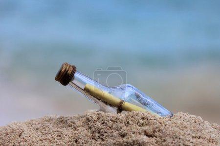 Photo pour Message dans la bouteille sur fond bleu - image libre de droit