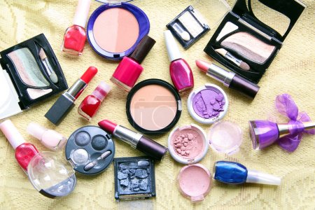 Make up assortment: lipsticks, nail polishes, blusher, eye shadows, foundation and powder of different colours