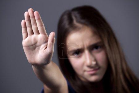 Photo pour Une jeune fille levant la main, pour dire non, ou arrêter, avec une expression grave froncée des sourcils . - image libre de droit