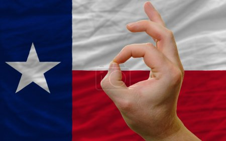 ok gesture in front of texas us state flag
