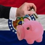 Man putting dollar into piggy rich bank flag of us...