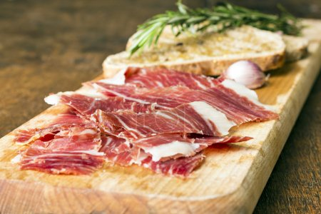Spanish ham with toasts as background