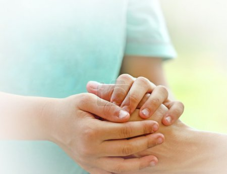 Son holds the hand of his mother