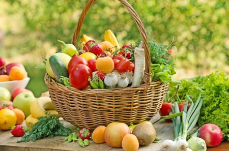 Wicker basket is full of fresh fruits and vegetables
