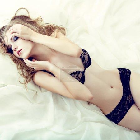 sensual girl sleeping in white bed