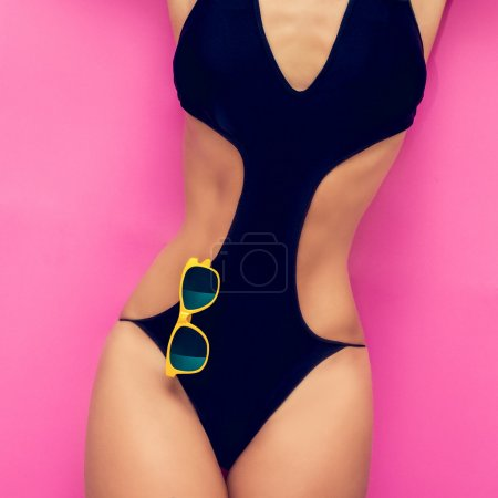 Fashion girl in a bathing suit on a pink background