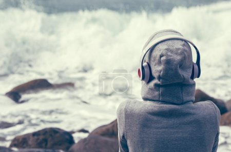 girl listening to music on the seafront