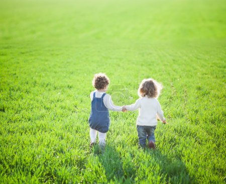 Photo for Children in beautiful spring green field - Royalty Free Image