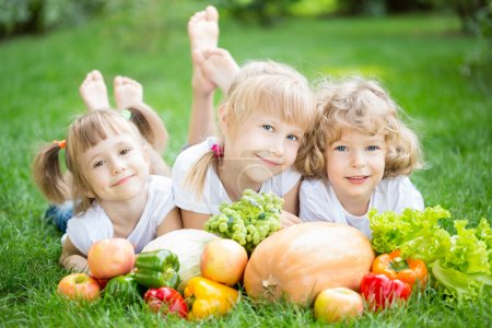 Photo for Group of happy children with fruits and vegetables lying on green grass in spring park. Healthy lifestyles concept - Royalty Free Image