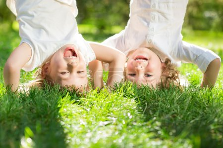 Photo for Happy children playing head over heels on green grass in spring park - Royalty Free Image