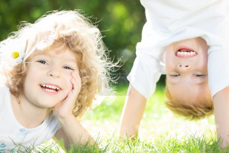 Photo for Happy children playing on green grass in spring park - Royalty Free Image