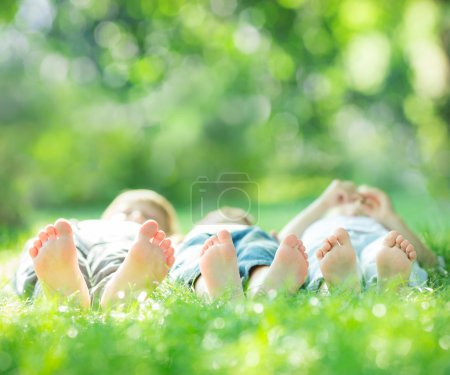 Photo for Happy family lying on green grass in spring park. Healthy lifestyle concept. Farmland vacations - Royalty Free Image