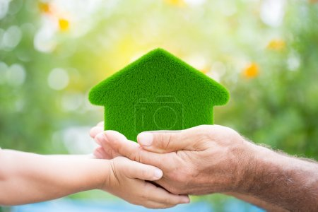 Photo for Family holding grass house in hands against green spring background. Environment protection concept - Royalty Free Image