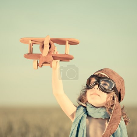 Photo for Happy kid playing with toy airplane against blue summer sky background. - Royalty Free Image