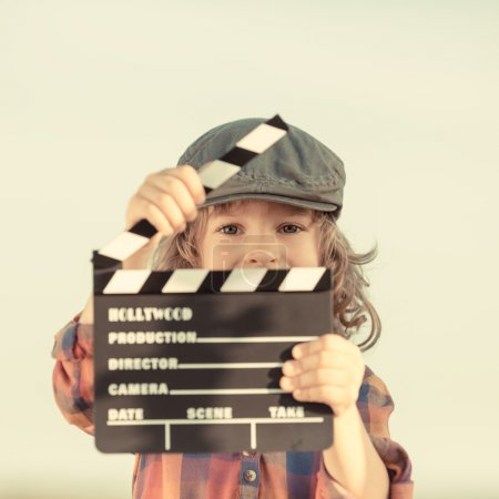 Photo for Kid holding clapper board in hands. Cinema concept. Retro style - Royalty Free Image