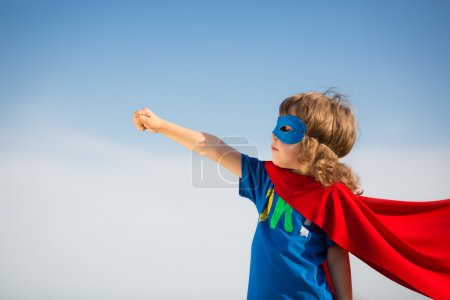 Photo for Superhero kid against blue sky background. Girl power concept - Royalty Free Image