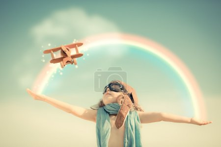 Photo for Happy kid playing with toy airplane against summer sky background - Royalty Free Image
