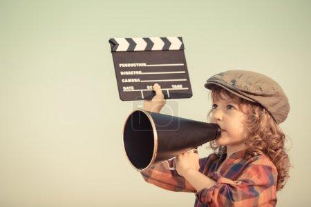 Photo pour Un gamin tenant une planche et criant à travers un mégaphone vintage. Concept de cinéma. Style rétro - image libre de droit